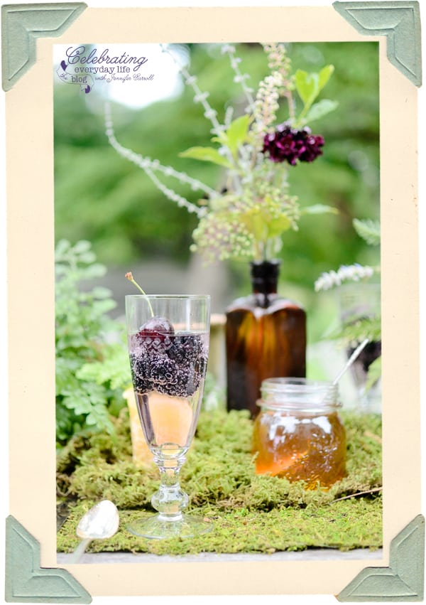 Blackberries and Cherries in Champagne, Lilac Champagne, Honey jar centerpiece, brown bottle centerpiece, brown bottle centerpiece, moss covered table, moss centerpiece, wildflower centerpiece, storybook table, fairy tale table, fern centerpiece, fern flower arrangement