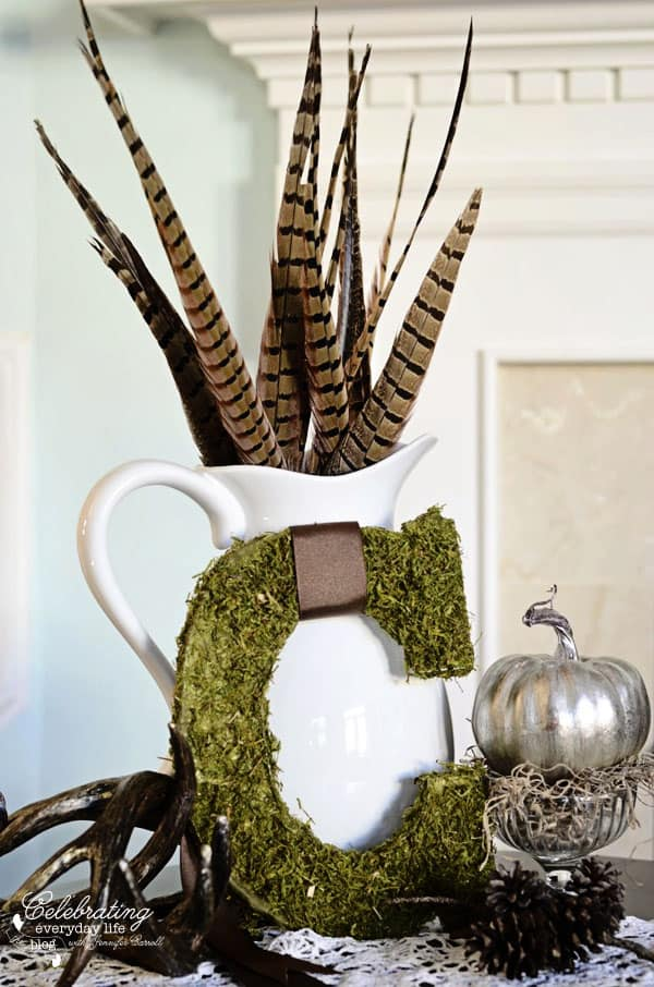 Mossy C with pheasant feathers in white pitcher