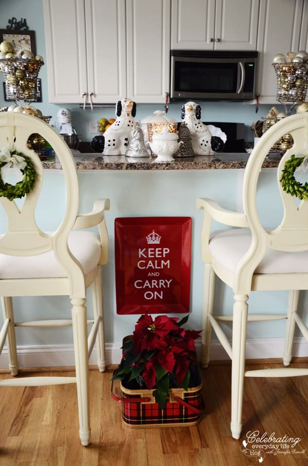 Celebrating Everyday Life Kitchen, Bar stools with boxwood wreaths, red keep calm and carry on tray, poinsettia in vintage plaid picnic basket