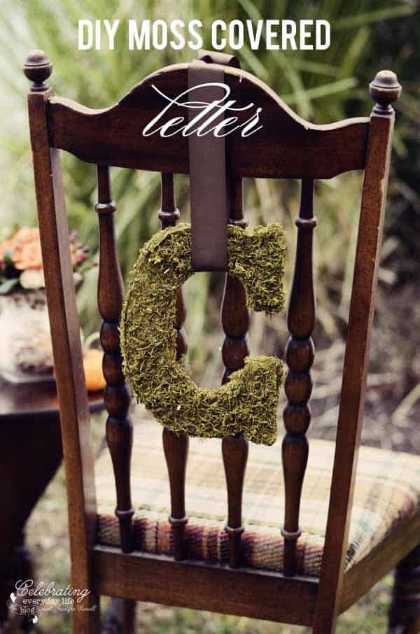 "Moss covered letter ""C"" hanging on the back of a brown chair with brown ribbon."