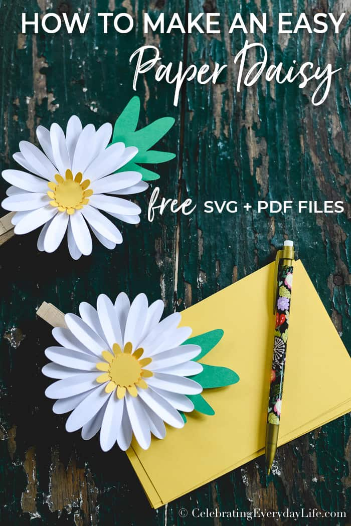 Easy Paper Daisy DIY sitting on a green rustic table with a yellow note card