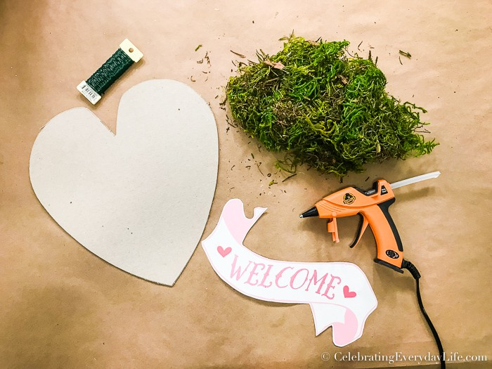 Supplies to make a moss heart laying on a table, it includes a chipboard heart, floral wire, a glue gun, moss and a welcome banner.