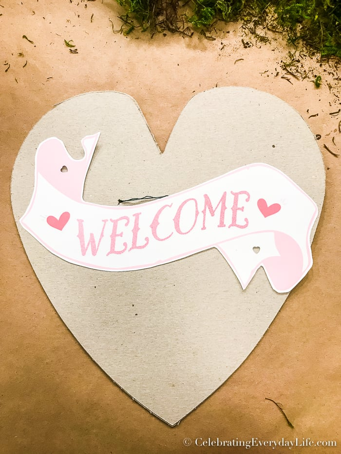 Welcome banner laying on heart for spacing purposes.