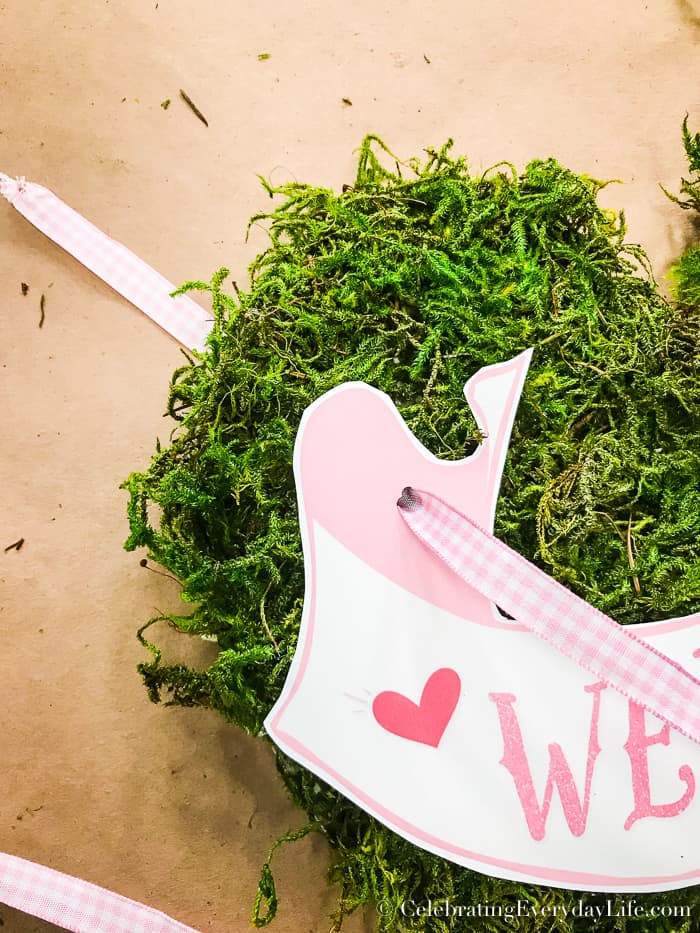 Pink ribbon pushed through banner and moss heart to attach it.