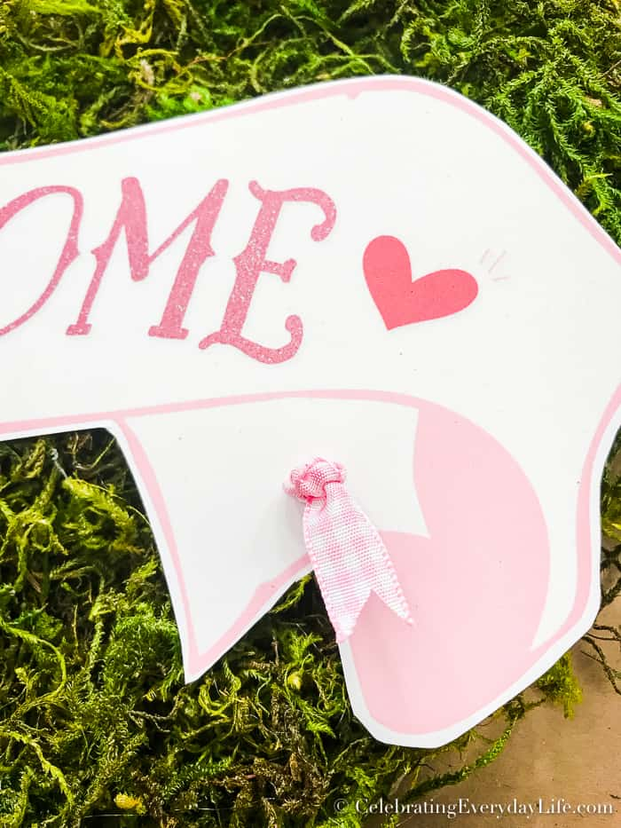 Pink ribbon tied in a pretty knot on a welcome banner on a moss heart.