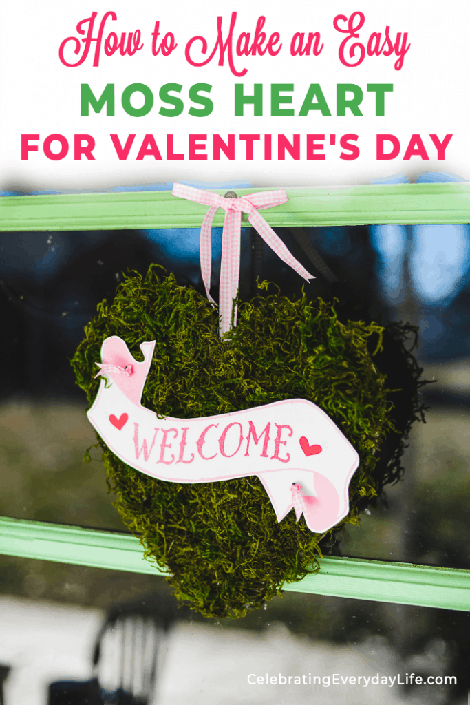 Moss Heart with welcome banner hanging from pink ribbon on a green and glass door.