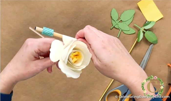 paper flower petal being rolled by hand with a dowel to curl the petals