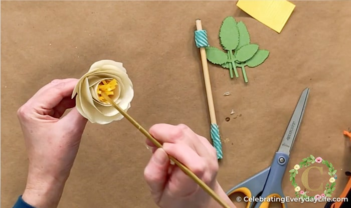 paper rolled flower with yellow center being attached by a knitting needle