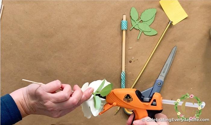 attaching green paper leaf to white paper rose with orange glue gun